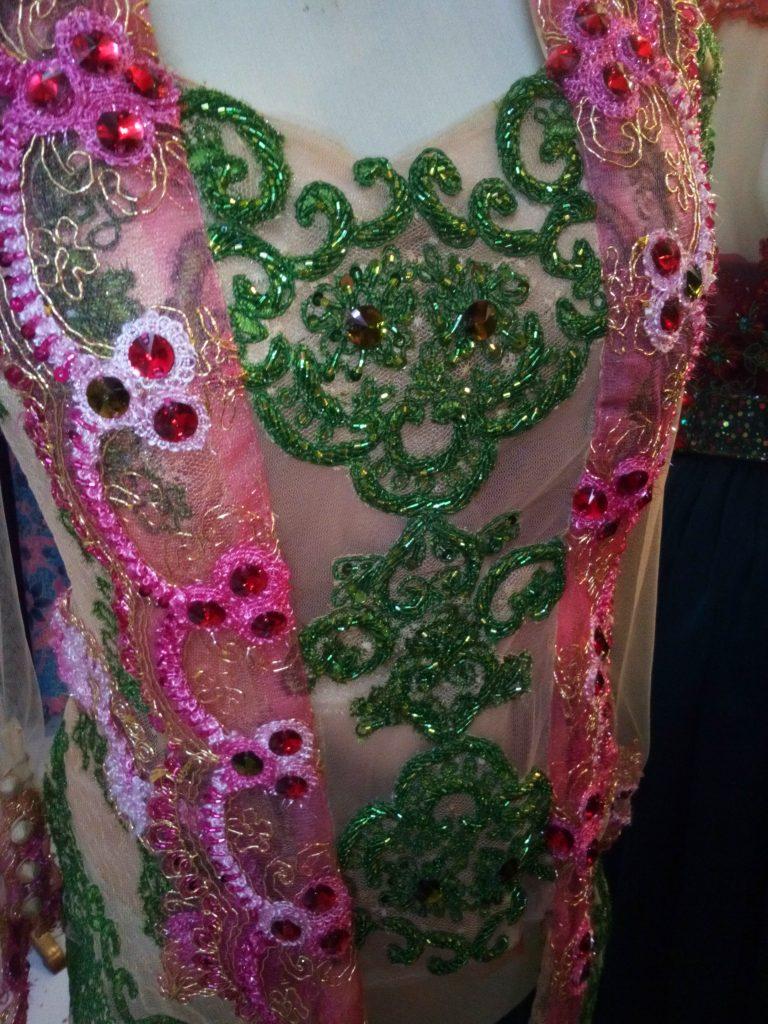 Kebaya kombinasi warna pink dan hijau dengan kerah kartini tampak bagian dada